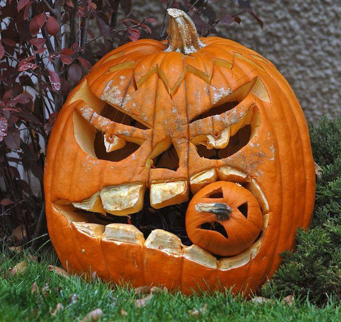 ein großer oranger halloween kürbis mit einem gruseligen hürbisgesicht mit gelben zähnen und großen augen, gruselige kürbisgesichter vorlagen