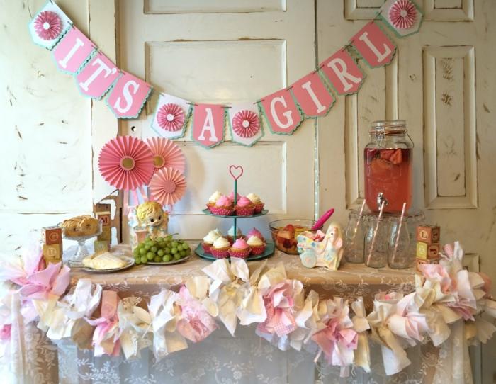 eine Girlande mit Buchstaben, rosa Cupcakes und Papierblumen, Deko für Babyparty