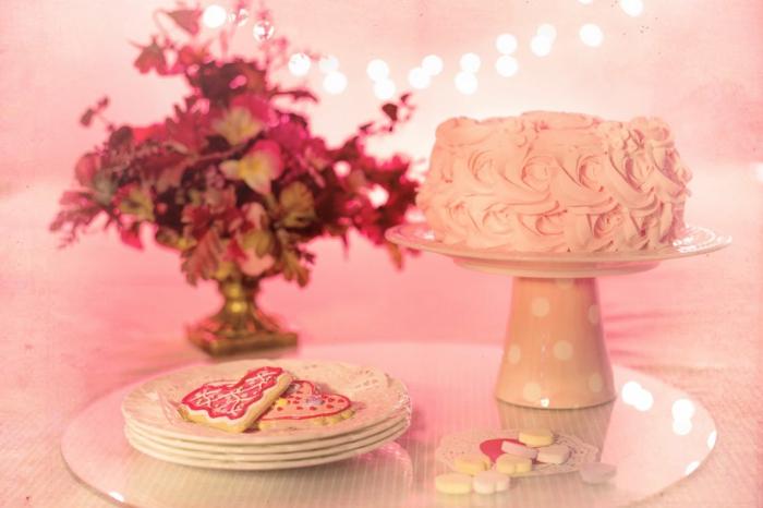 rosa Torte und rosa Plätzchen, rosa Bonbons, ein Blumenstrauß rosa Blumen, Deko für Babyparty