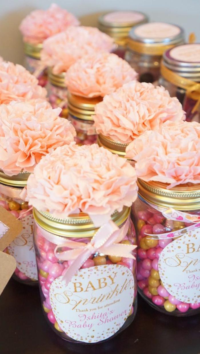 Babyparty Deko mit rosa Blumen auf Gläsern voller rosa Bonbons mit rosa Schleifen