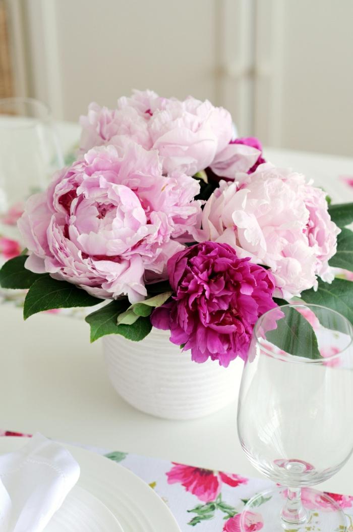 rosa und lila Blume in einer weißen Vase, Deko für Babyparty in der Mitte des Tisches