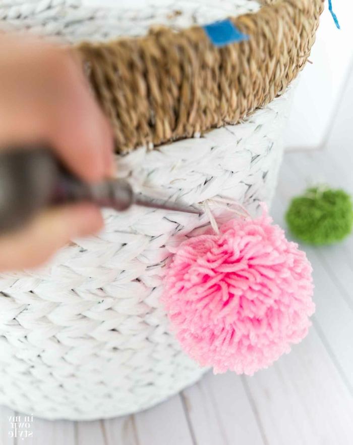 ein weißer Korb mit Pompon Deko in rosa Farbe, wie Sie die Pompons befestigen
