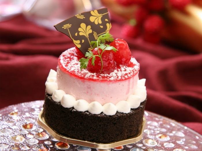 Schokoladen Kuchen mit rosa Creme, weiße Figuren, Himbeere und Stück Schokolade, Geburtstagstorte Rezept