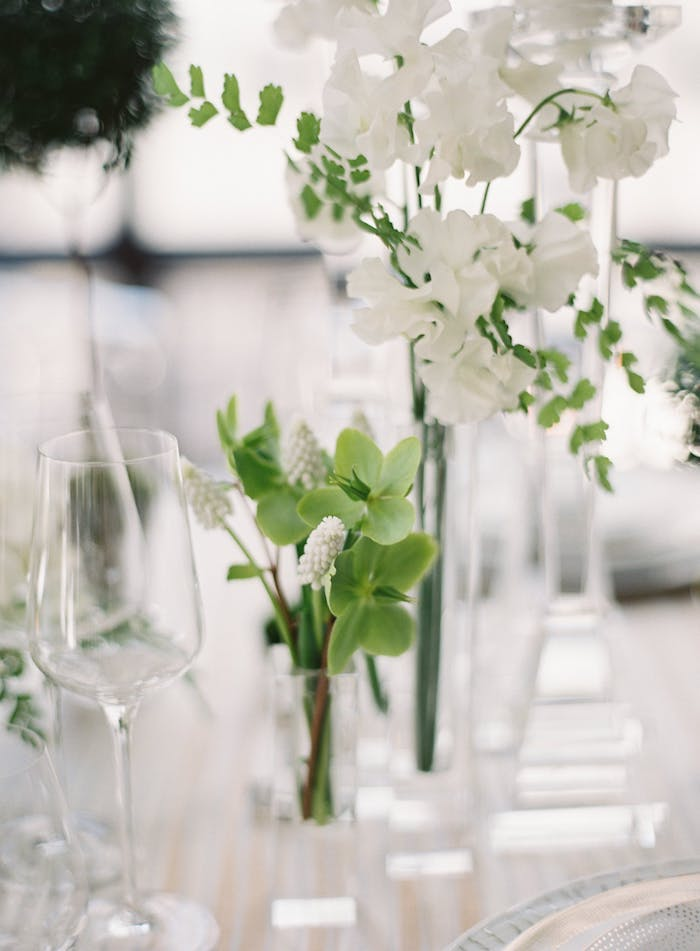 Weiße Blumen in Kristallvase, stilvolle Tischdeko für Hochzeit in Weiß
