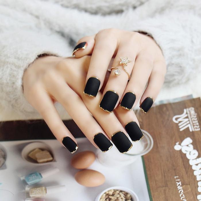 schöne gelnägel in schwarz und gold, goldener ring mit stern und steinen