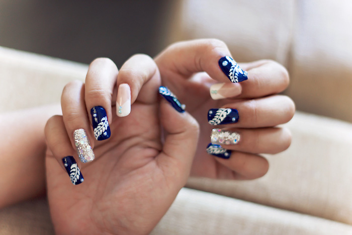 schöne gelnägel in weiß und blau, hochzeitsmaniküre mit dekorationen und glitzer