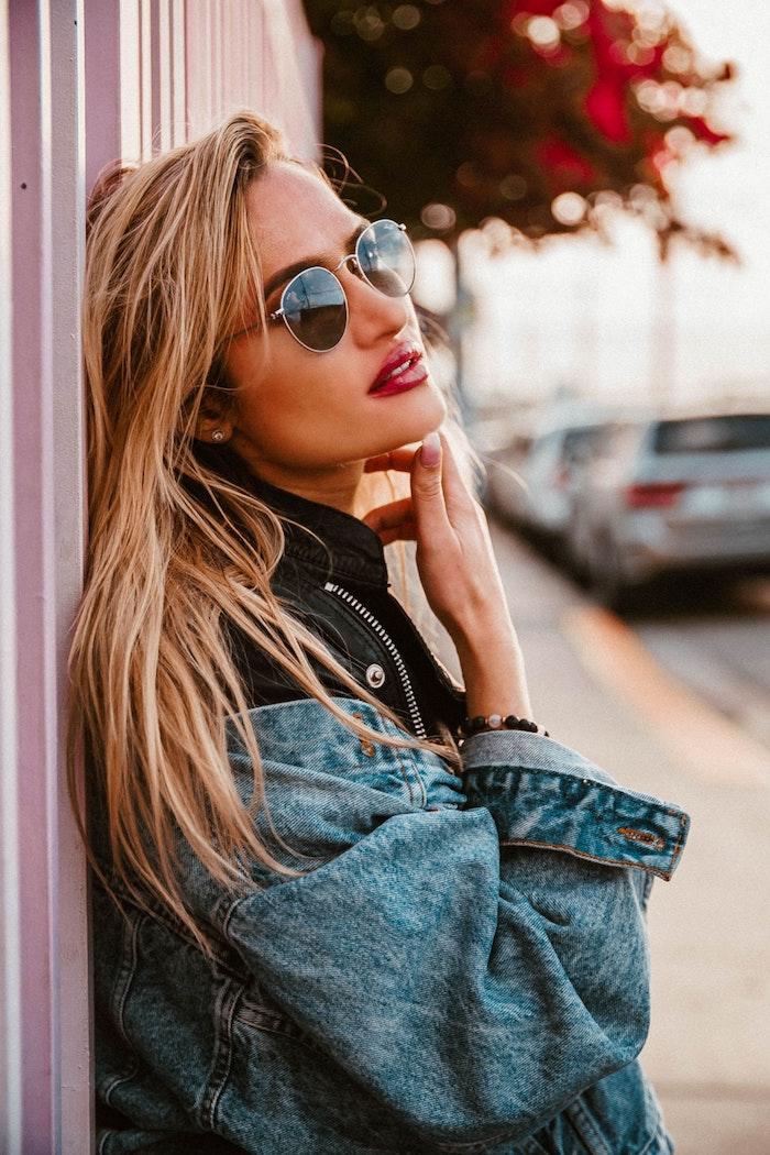 Goldblonde glatte Haare, Jeansjacke und Sonnenbrille, roter Lippenstift