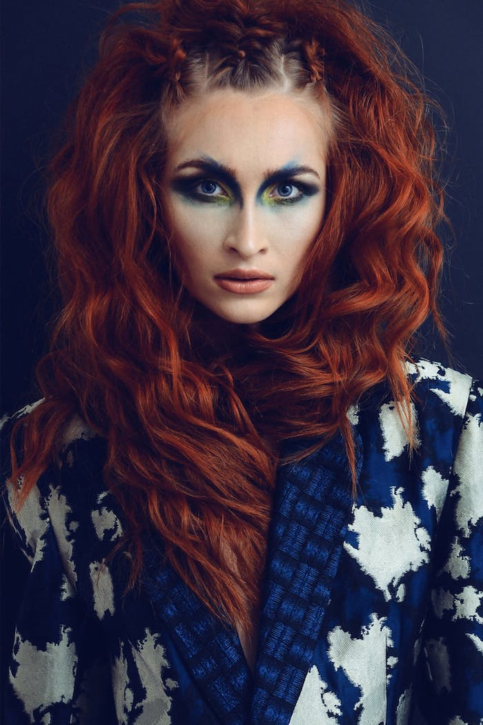 Rote wellige Haare, heller Hautteint, extravagantes Augen Make-up und matter Lippenstift, Mantel in Dunkelblau und Weiß