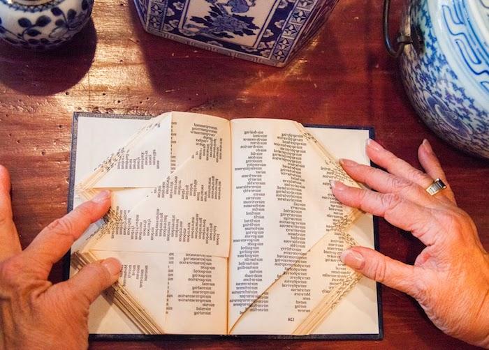 eine schritt für schritt diy anlietung bücher falten, zwei hände einer alten frau, eine hand mit einem ring, ein tisch aus holz und ein kleines buch mit einem blauen bucheinband mit gefalteten gelben seiten mit schwarzen buchstaben
