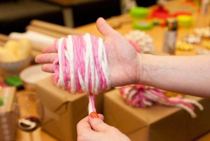 Schritt Zwei in der Anleitung von Pompons Basteln, Ihre Hand mit Garn umhüllen