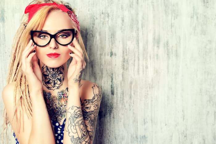 schwarze brikke und eine junge frau mit roten lipppen und mit schwarzen tattoos mit mandala motiven, tattoo arm frau