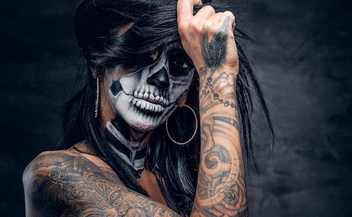 eine weiße totenkopf schminke einer frau mit ohrringen und mit händen mit weißen rosen tattoos und mit tattoos mit schwarzen federn, la catrina schminke