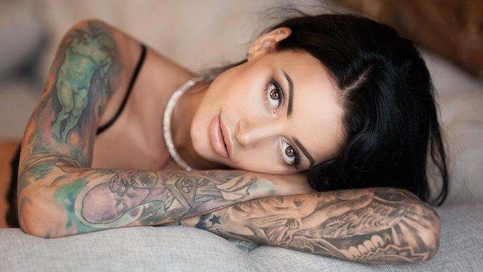 ein bett und eine junge frau mit einer weiß0en kette und mit zwei tattoos mit kleinen schwarzen sternen und totenkopf, tattoos frauen