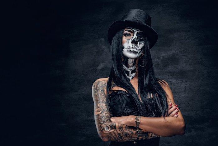 eine schwarze wand und eine junge frau mit einem weißen totenkopf schminke und einem schwarzen hut, tattoo arm frau mit schwarzen sternen und rosen