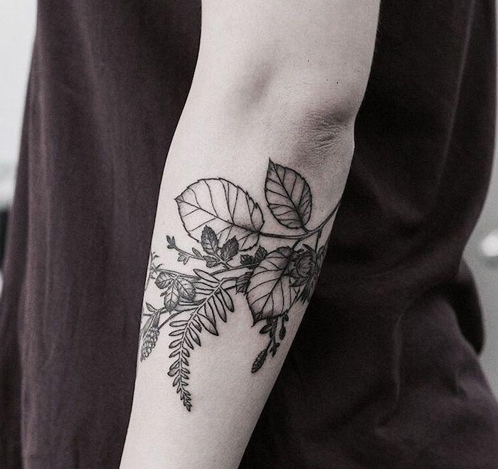 eine junge frau mit einer hand mit einem schwarzen tattoo mit vielen schwarzen und weißen blumen und blättern, frau tattoos ideen