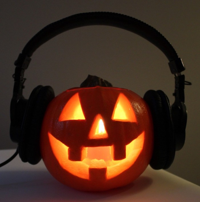 große schwarze kopfhörer und ein kleiner oranger kürbis halloween mit großen gelben augen und drei orangen großen zähnen, coole kürbisgesichter