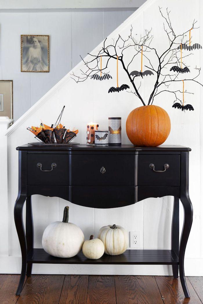ein oranger kürbis und schwarze äste mit vielen kleinen schwarzen und frauen diy fliegenden fledermäusen mit schwarzen flügeln au papier, halloween fledermaus selber basteln aus papier