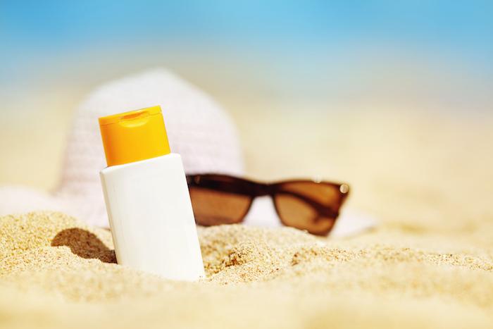 sonnenschutz - ein strand, meer, brille und eine sonnencreme
