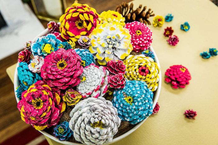 ein tisch und eine schüssel mit vielen blauen, gelben und violetten blumen aus bemalten tannenzapfen, tannenzapfen bemalen