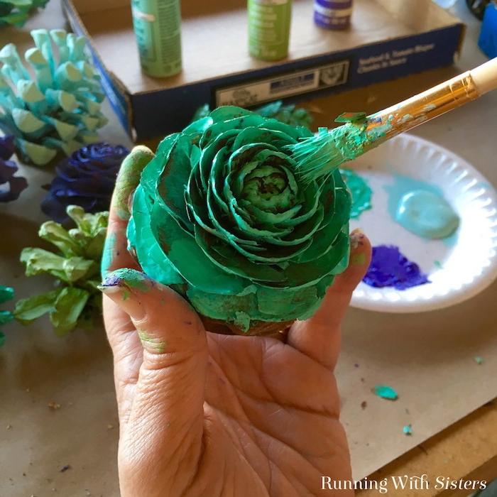 eine hand mit einer großen grünen bemalten rose und mit einem pinsel, ein weißer teller und kleine blaue und grüne bemalte tannenzapfen