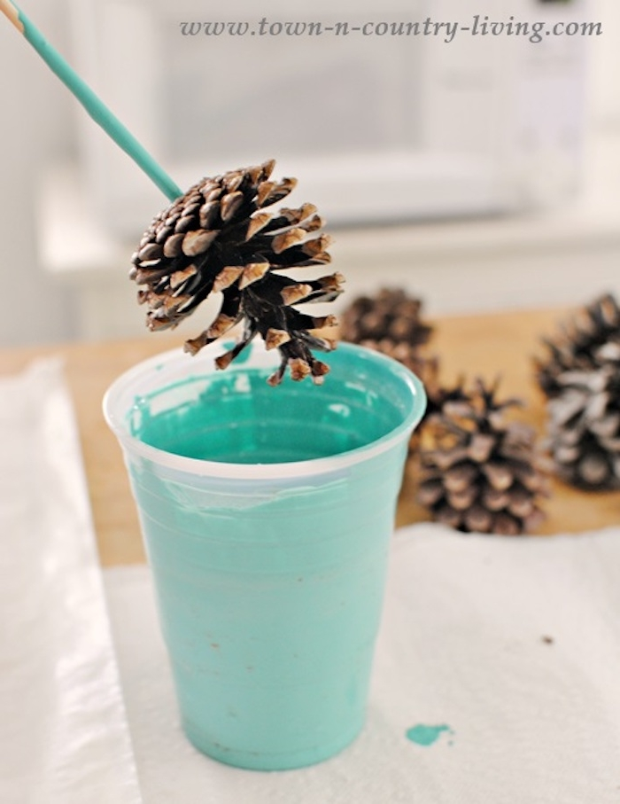 ein glas mit einer grünen farbe und ein kleiner brauner tannenzapfen, bastelideen für kinder, tannenzapfen bemalen anleitung