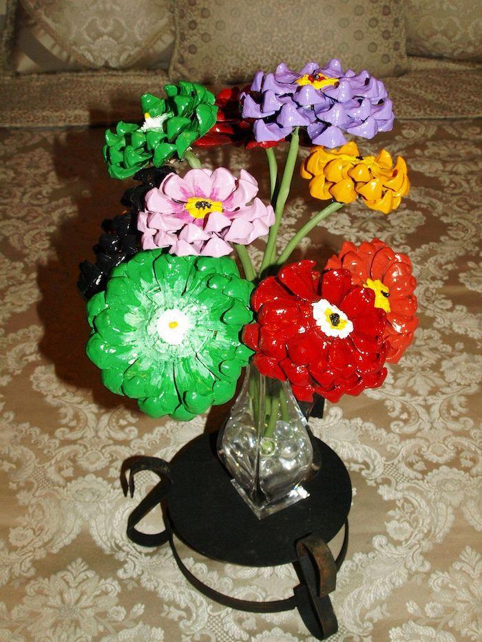 ein sofa und eine vase aus glas mit grünen, orangen, violetten und roten blumen aus bemalten kleinen tannenzapfen, basteln mit tannenzapfen