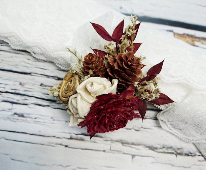 eine tischdeko mit vielen kleinen weißen rosen, roten und goldenen blumen und nzwei kleinen braunen tannenzapfen