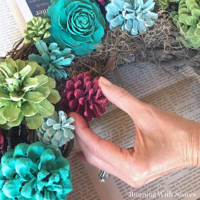 eine hand mit einem ring und ein kranz mit vielen gefalteten ästen und violetten, grünen und blauen blumen aus bemalten tannenzapfen, einen kranz selber basteln
