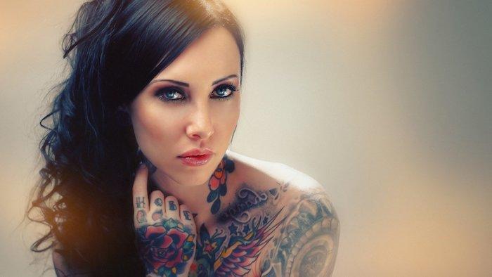 schwarze haare, eine junge frau mit vielen tattoos für frauen mit flügeln mit roten federn und mit vielen roten rosen und grünen blättern