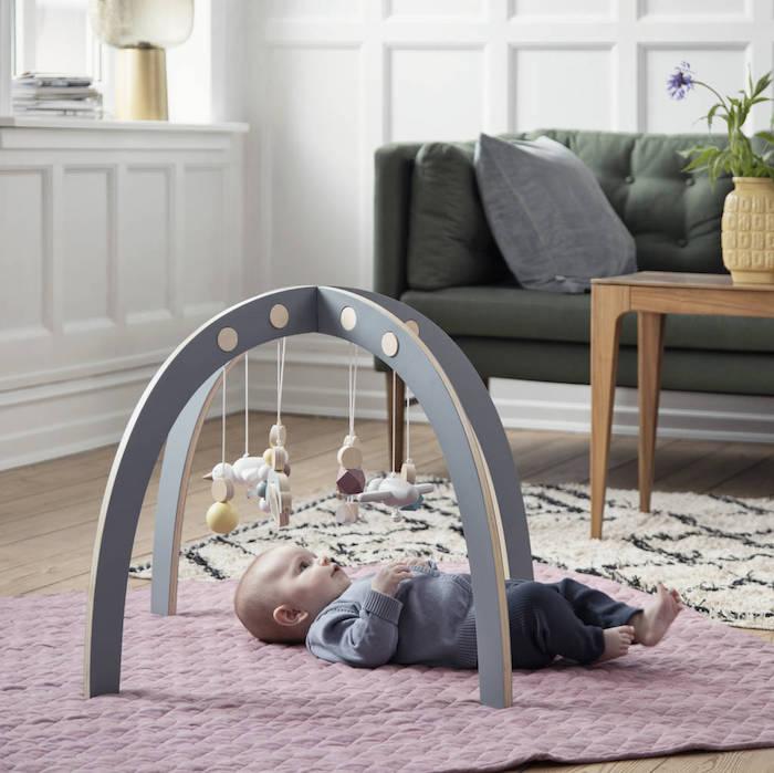 Süßes Baby liegt auf dem Boden und spielt mit Mobilen, Idee für Taufgeschenk