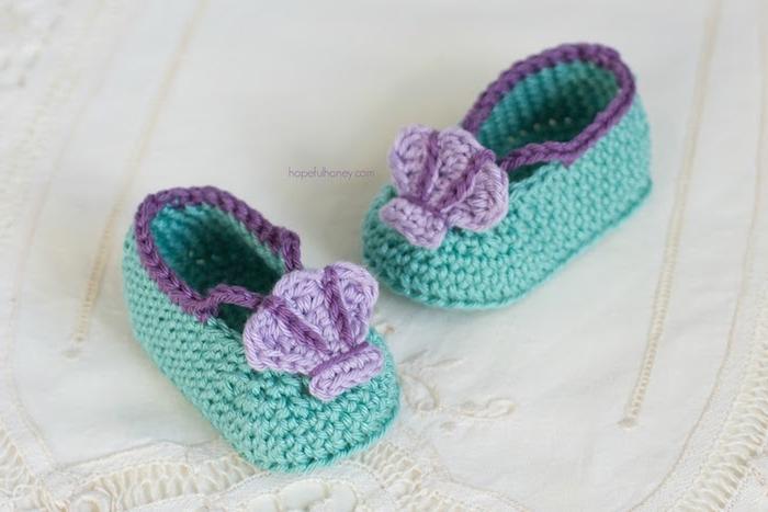 Selbstgestrickte grüne Babyschuhe mit lila Blumen, Taufgeschenk für Mädchen