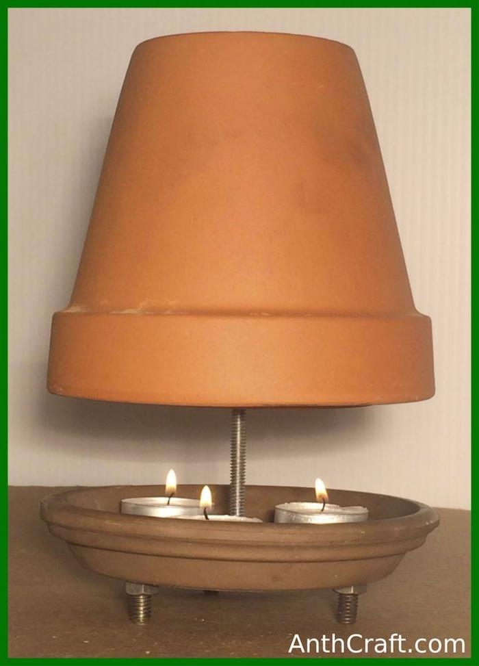 eine weiße wand und ein diy teelichtofen aus einem braunen teller und einem blumentopf aus keramik, eine schraube und drei kleine weiße teelichter, teelichtheizung