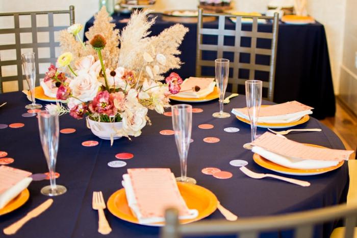 eine Tischdecke in dunkelblauer Farbe, gelbe Teller, hohe Gläser, Vase mit vielen Blumen