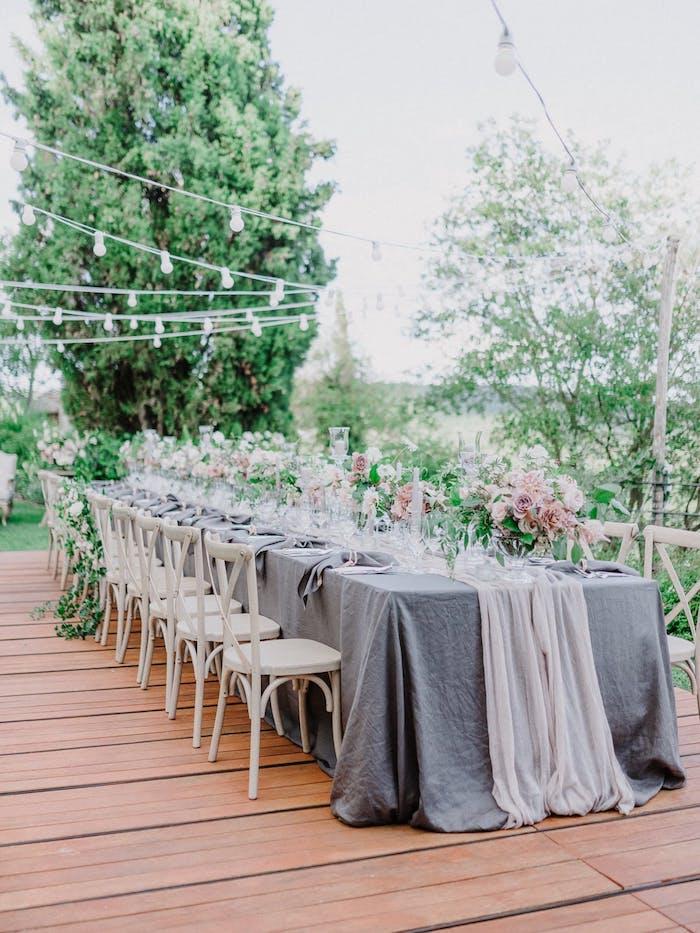 Hochzeitsfeier im Garten, Tischdekoration in Landhausstil, graue Tischdecke und Servietten, viele Blumen
