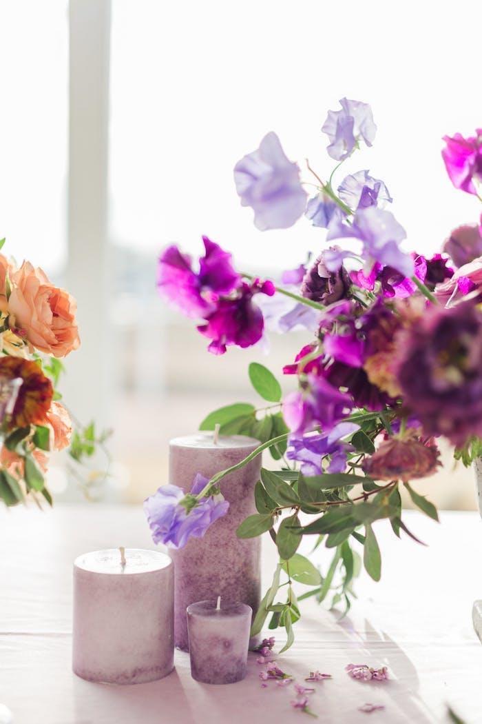 Ideen für Tischdeko in Lila, lilafarbene Duftkerzen und violette Blumen, Farbe des Jahres