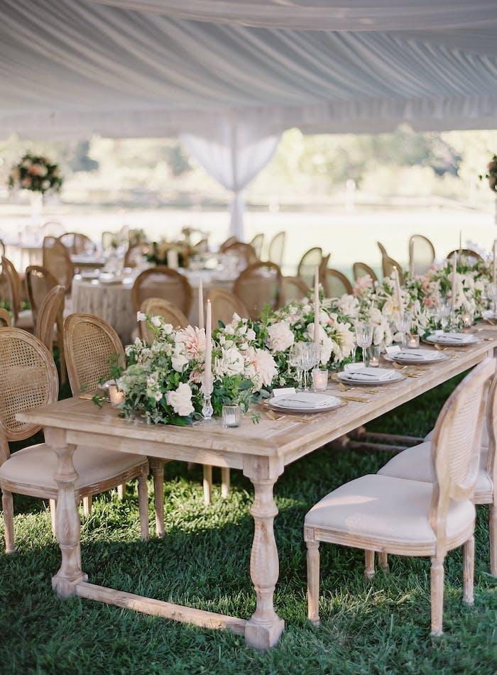 Hochzeitsdeko in Landhausstil, Holztisch und Stühle mit Altersspuren, weiße Blumen und Kerzen