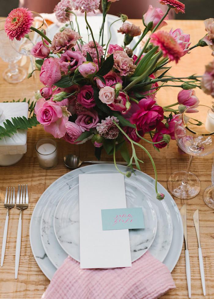 Wunderschöne Tischdeko mit vielen Blumen, Rosen Nelken und Pfingstrosen, rosafarbene Servietten und hellblaue Zettel mit den Namen der Gäste