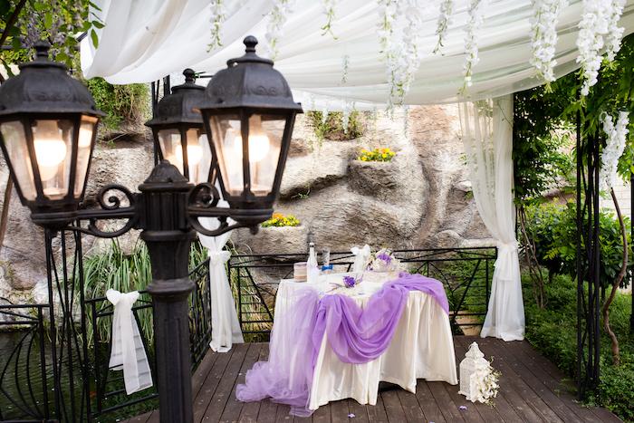Hochzeitsfeier im Garten, prachtvolle Dekoration, weiße Decke und lila Tüll