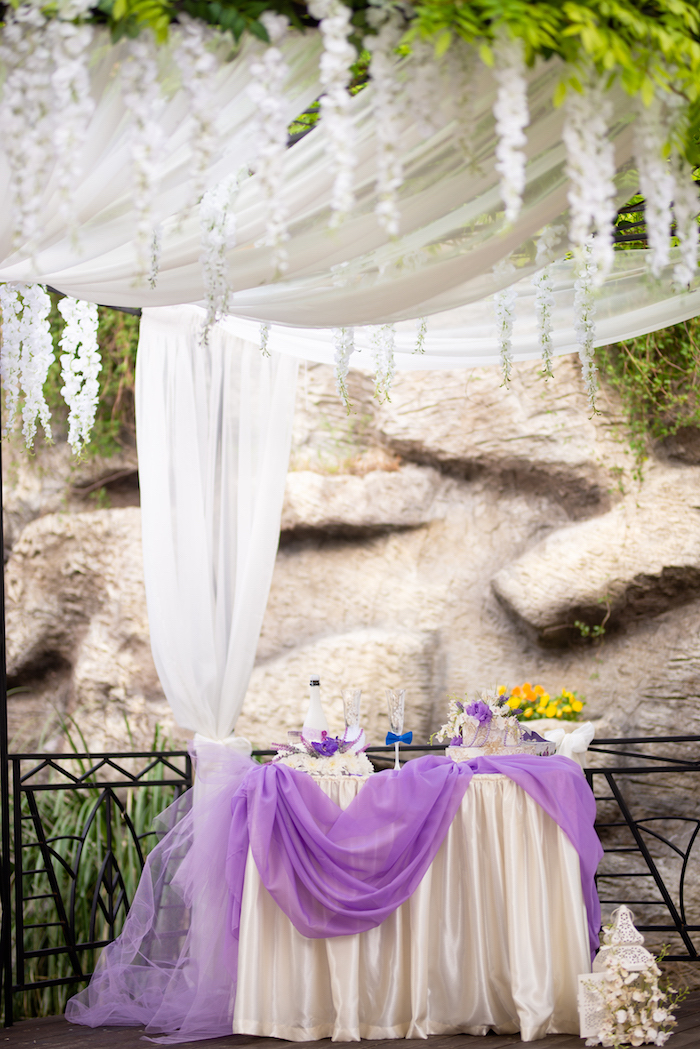Hochzeitsfeier im Garten, weiße Tischdecke mit lila Tüll, Weinglas mit blauer Fliege