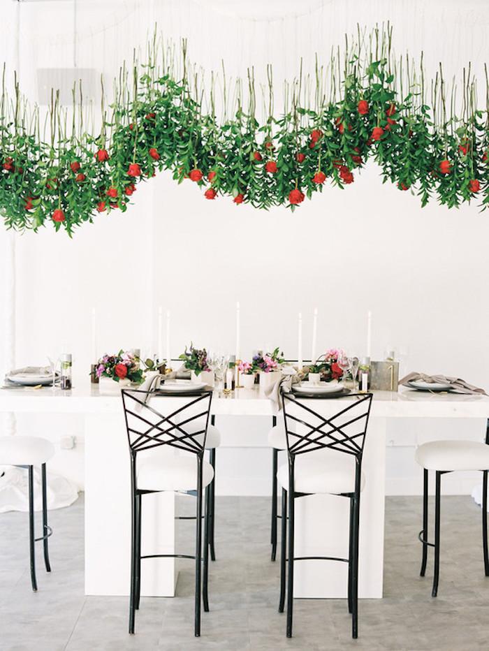 Kreative und ausgefallene Hochzeitsdekoration, rote Rosen in der Luft, weiße Kerzen