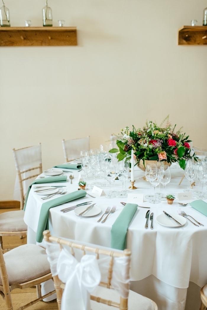Stilvolle Tischdekoration für Hochzeit, weiße Tischdecke und grüne Servietten, viele Blumen