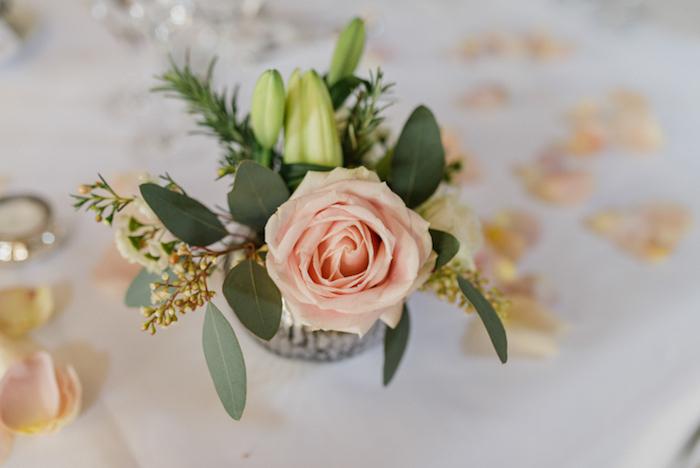 Kleiner Strauß aus Rosen und Lilien, Blütenblätter auf dem Tisch, weiße Tischdecke