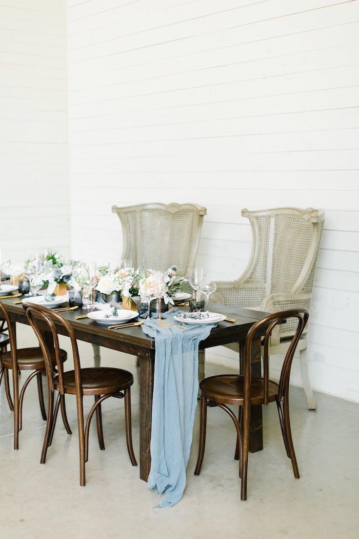 Hochzeitsdekoration in Vintage Stil, Tisch und Stühle mit Altersspuren, blaue Tischdecke und weiße Blumen