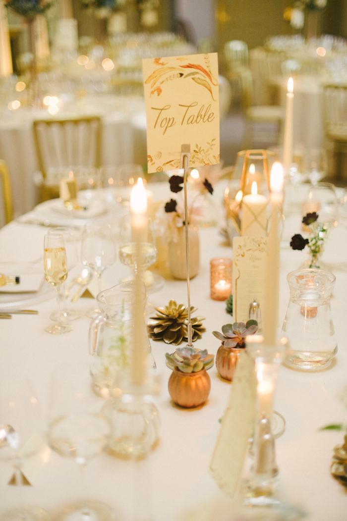 Stilvolle Tischdekoration für herbstliche Hochzeit in Golden, kleine Kürbisse und Zapfen