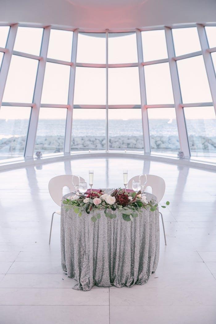 Idee für ausgefallene Tischdekoration, silberne Tischdecke, viele Rosen, Weingläser aus Kristall