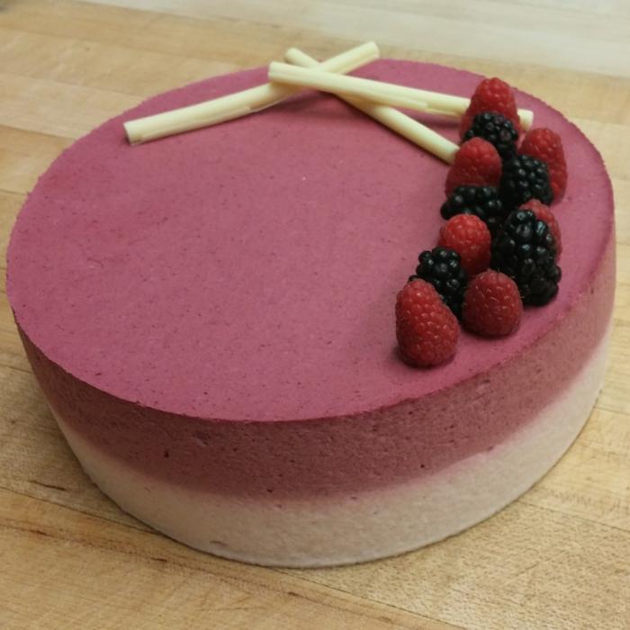 zwei rosa Schichte von Creme, Himbeeren als Deko, weiße Stangen, Geburtstagstorte Rezept