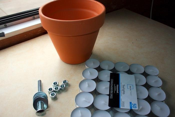 eine teelichtheizung, einen teelichtofen selber machen, ei fenster und ein blumentopf aus keramik, viele kleine weiße teelichter, schrauben und bolzen au metall