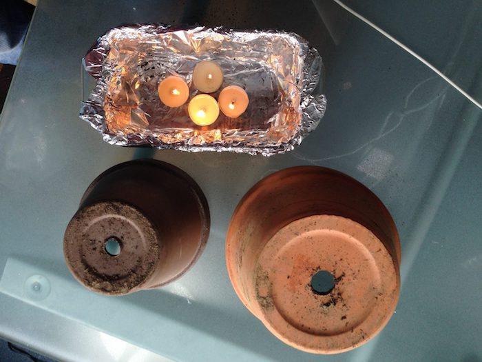 ein tisch aus glas und zwei große braune blumentöpfe aus keramik und vier kleine weiße teelichter, einen teelichtofen selber bauen, eine teelichtheizung