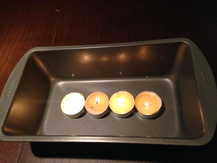 eine teelichtheizung schaffen, ein tisch aus holz und vier kleine weiße teelichter und ein schwarzes backblech