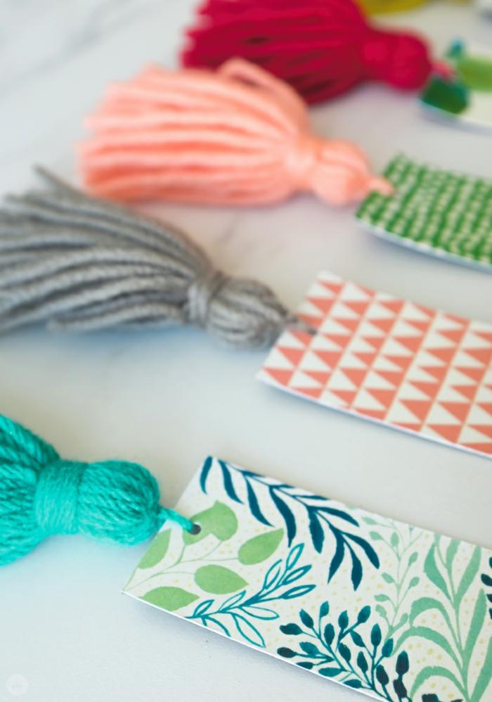 vier DIY Lesezeichen mit Quasten in verschiedenen Farben, bunten Kartons